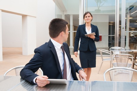 Positive coworkers holding tablets and meeting in outdoor cafe. Business man sitting at desk and looking back at woman who is walking to him. Colleagues concept. Stockfoto
