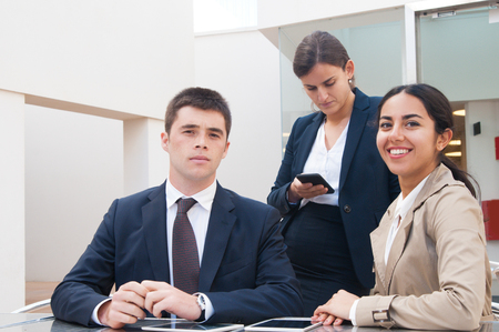 Positive young business people posing at camera at desk outdoors. Business man and women standing and sitting at cafe table. Business people portrait concept. Front view. Stockfoto