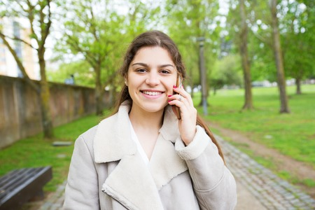 Happy beautiful young woman calling on phone in park. Lady wearing jacket, looking at camera and standing with walkway and green trees in background. Communication and nature concept. Front view.