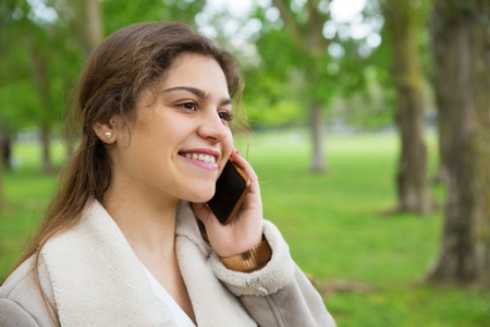 Happy pretty woman calling on smartphone in park. Lady wearing jacket, talking on mobile phone and standing with green grass and trees in background. Communication and nature concept.