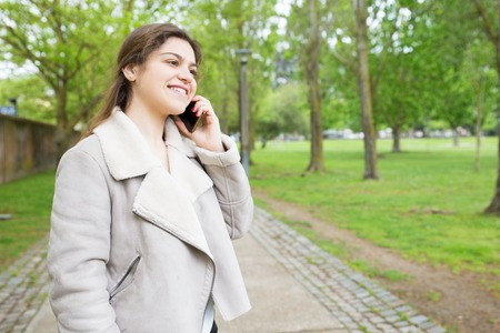 Happy pretty young woman calling on smartphone in park. Lady wearing jacket, talking on mobile phone and standing with walkway and green trees in background. Communication and nature concept. Stockfoto