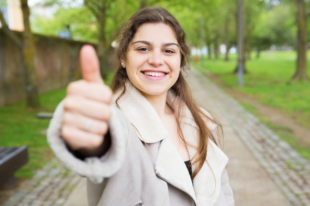 Happy pretty young woman showing thumb up in park. Happy lady wearing jacket, looking at camera and standing with walkway and green trees in background. Recommendation concept. Front view.