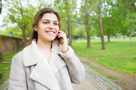 Happy pretty young woman talking on smartphone in park. Lady wearing jacket, calling on mobile phone and standing with walkway and green trees in background. Communication and nature concept.