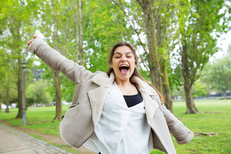 Cheerful pretty young woman spreading arms and screaming in park. Excited lady wearing jacket, looking at camera and having fun with green trees in background. Happiness concept. Front view.