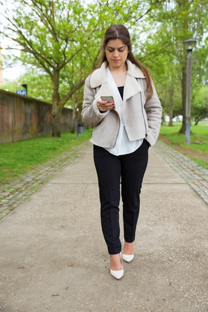Serious pretty young woman texting on smartphone in park. Lady wearing jacket, using gadget and walking on walkway with green trees in background. Communication concept. Front view. Stockfoto