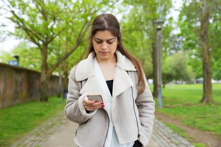 Serious pretty young woman using smartphone in park. Lady wearing jacket, texting on gadget and standing with walkway and green trees in background. Communication and nature concept. Front view.
