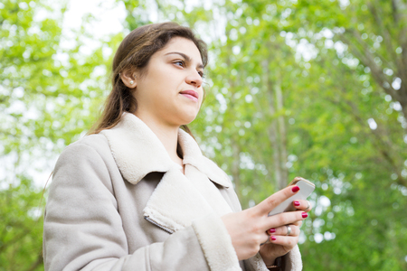 Pensive pretty young woman using smartphone in park. Lady wearing jacket, texting on gadget and standing with green trees in background. Communication and nature concept. Stockfoto