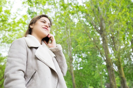 Smiling pretty young woman calling on smartphone in park. Lady wearing jacket, talking on mobile phone and standing with green trees in background. Communication and nature concept. Stockfoto