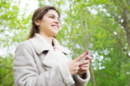 Smiling pretty young woman using smartphone in park. Lady wearing jacket, texting on gadget and standing with green trees in background. Communication and nature concept.