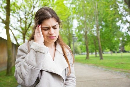 Tired young woman touching temple in park. Lady wearing jacket and standing with closed eyes, walkway and green trees in background. Headache concept. Front view. Stockfoto