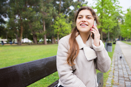 Cheerful girl speaking on phone in park and looking into distance. Smiling young woman in warm jacket sitting on bench and talking on cell. Communication or waiting in park concept