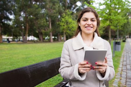 Cheerful Latin girl relaxing in park. Young woman in warm jacket sitting on bench and using tablet, grass and trees in background. Communication concept