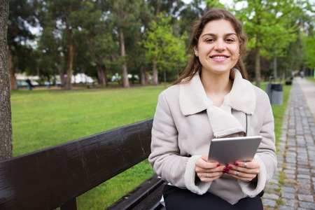 Positive student girl enjoying internet connection in park. Young woman in warm jacket sitting on bench and holding tablet, grass and trees in background. Wireless connection concept