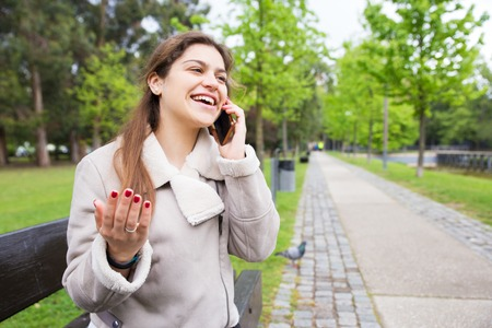 Happy student girl excited with funny phone talk. Young woman in warm jacket sitting on bench in park, speaking on cell, gesturing with hand and laughing. Nice phone talk concept