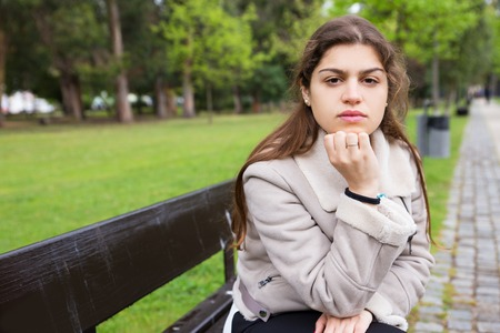Pensive Latin girl waiting someone in park. Young woman in warm jacket sitting on bench outdoors and looking at camera. Waiting in park concept