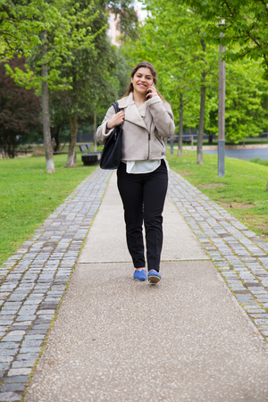 Happy positive girl walking down footpath and speaking on phone. Young woman in warm jacket enjoying nature in park and talking on cellphone. Communication concept