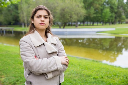 Serious student girl posing in park near pond. Outdoor portrait of young woman in warm jacket with folded arms. Female portrait concept