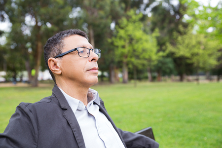 Pensive middle aged man in eyeglasses relaxing outdoors. Office employee spending work break in park, sitting on bench and looking away. Outdoor break concept
