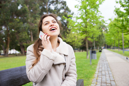 Joyful girl chatting on phone and totally excited with talk. Young woman in warm jacket sitting on bench in park and speaking on cellphone. Communication or good news concept Stockfoto