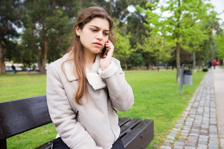 Shocked upset student girl talking on phone and learning bad news. Stressed young woman in warm jacket sitting on bench in park and speaking on cell. Bad news or communication concept