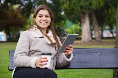 Joyful Latin college girl with tablet drinking takeaway coffee in park. Young woman in warm jacket sitting on bench in park, holding gadget and smiling at camera. Internet connection outdoors concept