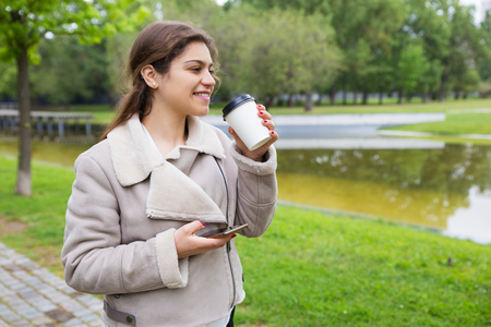 Smiling relaxed girl with phone drinking tasty coffee in park. Young woman in warm casual jacket standing near pond, holding smartphone and enjoying takeaway drink. Outdoor leisure concept Stockfoto