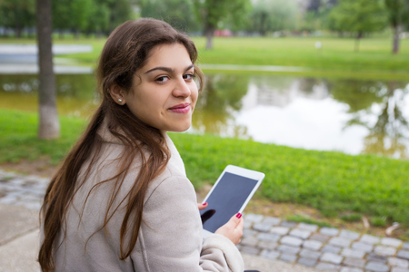 Positive Latin girl chatting online outdoors. Back view of young woman sitting on bench in park, holding tablet, turning around and smiling at camera. Communication concept Stockfoto