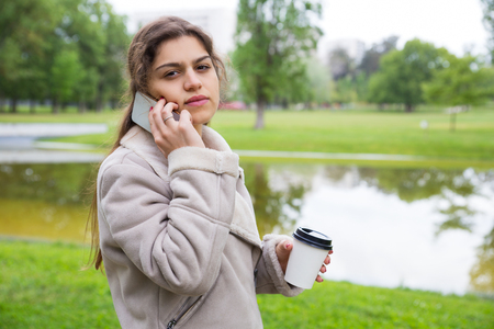 Pensive girl in warm jacket talking on phone in park. Young woman standing on grass near pond, holding coffee cup and speaking on cell. Communication concept