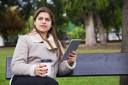 Pensive Latin girl reading book on tablet screen in park. Young woman in warm jacket sitting on bench, drinking coffee and holding gadget. Outdoor coffee break concept Stockfoto