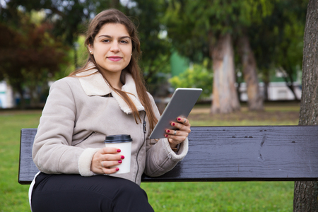 Positive Latin student enjoying coffee break in park. Young woman in warm jacket sitting on bench in park, holding tablet and paper cup and smiling at camera. Coffee break outdoors concept