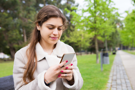 Positive peaceful girl texting message on mobile phone. Young woman in warm casual jacket sitting on bench in park and using phone. Connection outdoors concept