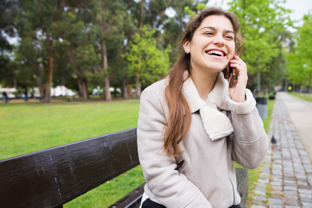 Happy joyful girl enjoying funny phone talk and laughing. Young woman in warm jacket sitting on bench in park and speaking on cell. Communication or good news concept