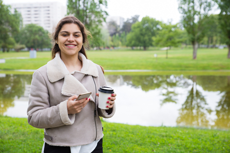 Happy joyful girl with phone enjoying takeaway coffee in park. Young woman in casual jacket standing on grass and holding paper cup and smartphone. Outdoor coffee break concept