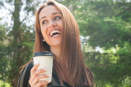 Happy cheerful girl walking in park with takeaway coffee. Closeup of young woman holding takeaway cup, looking away and laughing. Outdoor coffee break concept
