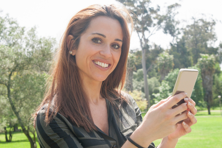 Happy cheerful lady using smartphone outdoors. Beautiful young woman standing in park, holding cellphone and smiling at camera. Mobile internet connection concept Stockfoto