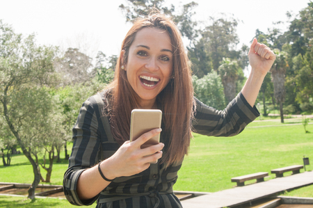Happy cheerful lady with smartphone excited with extremely great news. Woman holding smartphone, raising fist in joy, looking at camera and laughing. Victory concept
