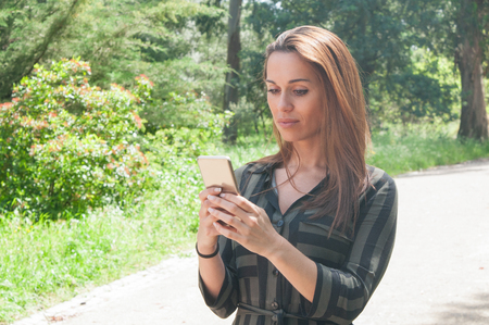 Focused business lady typing message on smartphone outdoors. Young woman standing in park and using cellphone. Communication concept