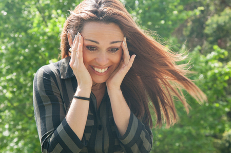 Happy overjoyed girl seeing something cute or getting good news. Surprised shocked woman in casual touching head, smiling and looking down. Joy or good news concept