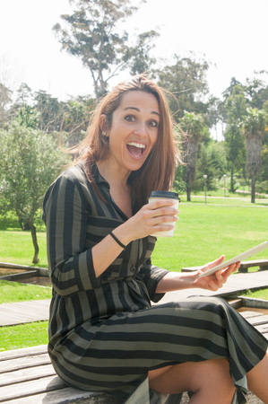Happy excited woman with coffee and tablet surprised with good news. Pretty lady sitting on park bench, holding pad and paper cup, smiling at camera and shouting with joy. Good news concept