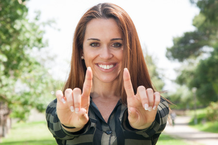 Cheerful girl showing index fingers at camera. Young woman standing outdoors and holding empty copy space. Advertising concept