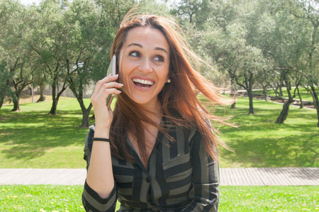 Joyful positive young woman speaking on phone outdoors. Happy beautiful lady speaking on smartphone in park. Communication and good news concept Stockfoto