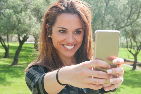 Joyful excited young woman taking selfie in park. Beautiful lady holding smartphone in outstretched arms and smiling at screen. Self portrait concept