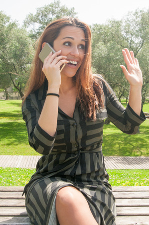 Positive beautiful young woman speaking on cell and greeting someone outdoors. Cheerful lady in casual sitting on bench in park and talking on mobile phone. Positive phone talk concept