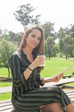 Positive relaxed woman enjoying leisure time and coffee break outdoors. Beautiful Caucasian lady in casual sitting on park bench, holding tablet and takeaway cup and smiling at camera. Leisure concept