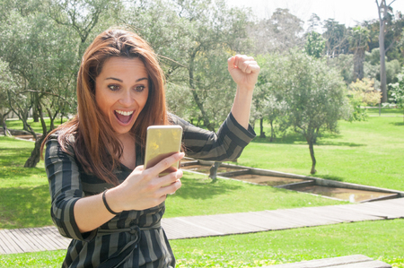 Overjoyed lady with mobile phone celebrating victory. Happy woman staring at phone screen in surprise, raising fist in win gesture and shouting with joy. Great news or triumph concept Stockfoto