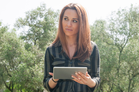 Serious pensive woman walking in park and using tablet. Beautiful Caucasian lady in casual standing against trees, holding gadget and looking away. Connection outdoors concept