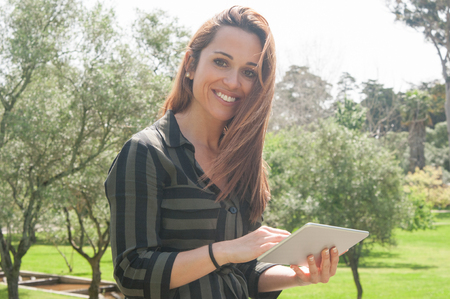 Happy positive woman enjoying high speed internet connection outdoors. Attractive Caucasian lady in casual walking in park, holding tablet and smiling at camera. Wireless connection concept