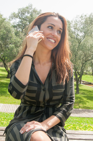 Happy positive young woman chatting on cell outdoors and getting good news. Joyful attractive lady sitting on bench in park and talking on cellphone. Mobile communication concept