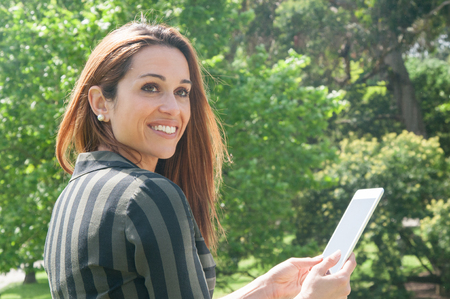 Happy cheerful business lady using tablet in park. Smiling beautiful Caucasian woman in casual sitting on bench, holding tablet and looking away. Wireless connection concept Stockfoto