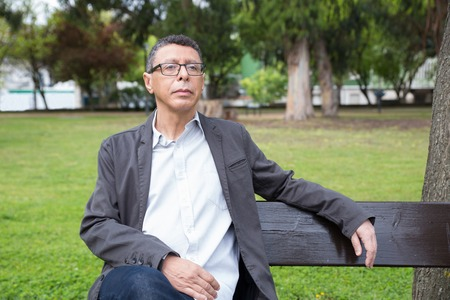 Calm middle-aged man sitting and relaxing on bench in park. Guy wearing casual clothes and looking away with green lawn and trees in background. Relaxation and nature concept. Front view.